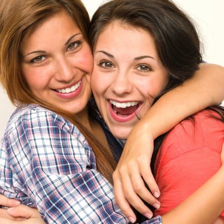 20244527 - caucasian sisters friends embracing and  laughing at camera